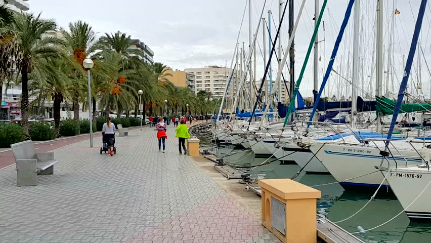 PALMA DE MALLORCA, SPAIN - OCTOBER 2015. A walk on autumn day on the city's waterfront, which is also a dock for private yachts. | Shutterstock HD Video #14666926