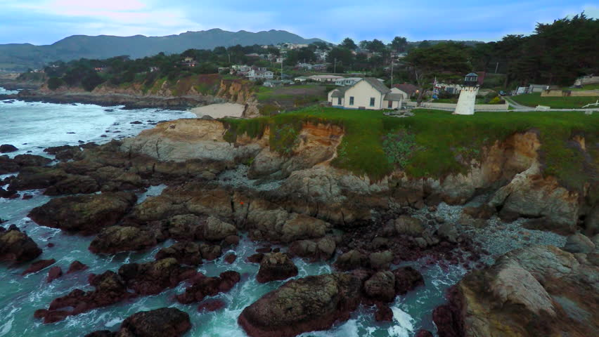 4k Aerial birds eye overhead of California Coastal ocean lighthouse on the cliffs over the pacific ocean. Moves from right to left over the ocean waves, shore rocks, looking back at the lighthouse.