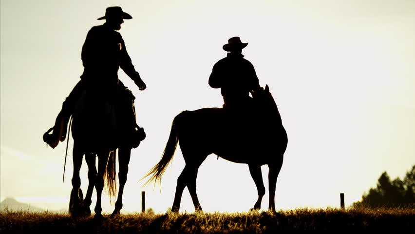 Silhouette of cowboy riders in forest wilderness area at sunset Canada #14685346