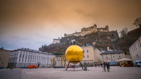 SALZBURG - FEBRUARY 18: Time Lapse in 4K of people walking in front of the golden ball at the Kapitelplatz with view on the Hohensalzburg February 18, 2016 in Salzburg, Austria.