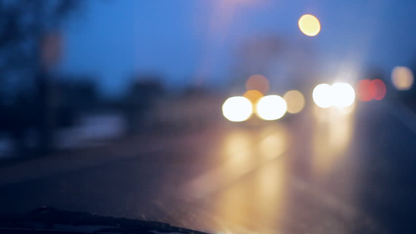 Driving at night. Windshield view and blurred cars in city. Illuminated front car window with blurred city traffic on town streets.