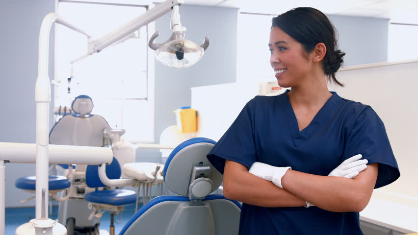 Smiling dentist by her equipment at the dental office
