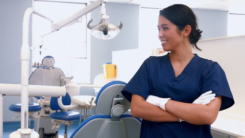Portrait of smiling mixed-race dentist by her equipment at the dental office
