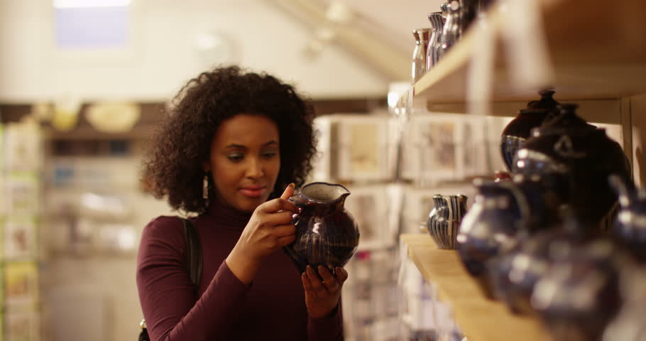 Woman looking at pottery for sale at her local shop. | Shutterstock HD Video #14730415