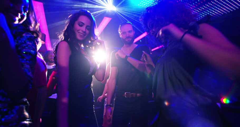 Party flythrough shot of young multi-ethnic group of people and friends dancing to cool music with disco lights in a nightclub for entertainment | Shutterstock HD Video #14730778