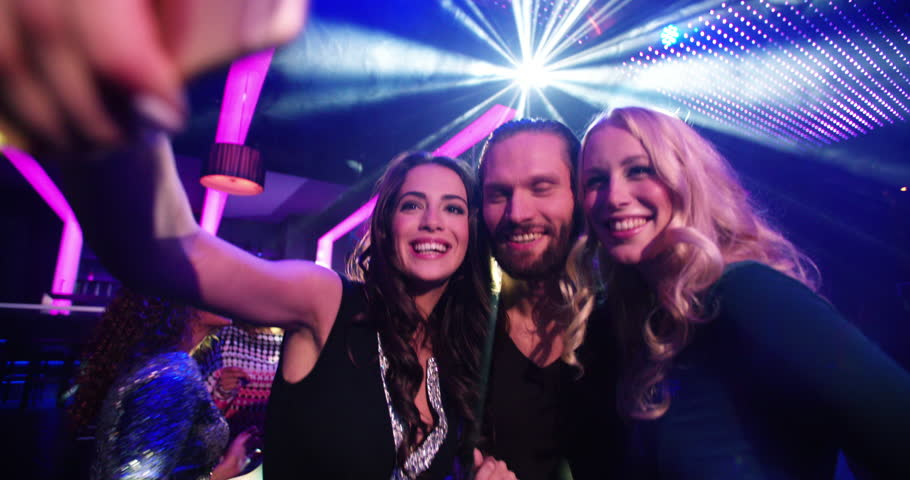 Young smiling attractive multi-ethnic party people taking a selfie at the nightclub with music and disco lights as well as friends in the background