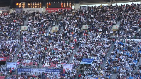 SEOUL, SOUTH KOREA - 11 OCTOBER 2015: Audience on a massive grandstand, with a board showing the interim score of a baseball game in the Jamsil stadium, Seoul, South Korea