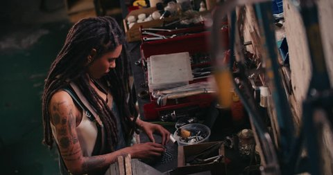 High angle image of an afro-american craftswoman working carefully at her work bench surrounded by well-used tools, assembling bicycle parts