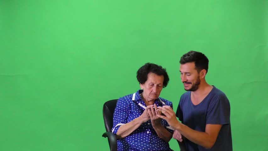 Old lady and young male playing with smart phone. | Shutterstock HD Video #14757436