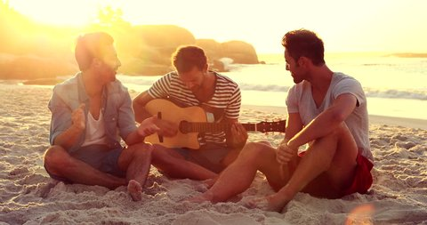 Happy friends playing guitar at the beach
