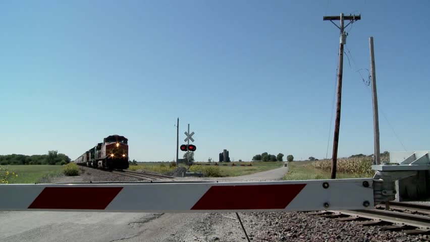A freight train speeds past a gated railroad crossing.