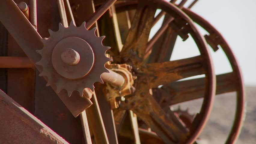Old cogwheels rust in the sun at an abandoned mine.