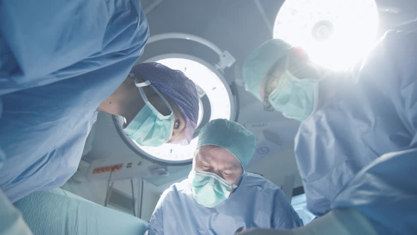 Turning Lights On in Operating Room. Team of Doctors and Nurses over Patient. Patient Point of View. Shot on RED Cinema Camera.