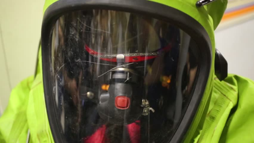 Male head in protective helmet of green chemical suit