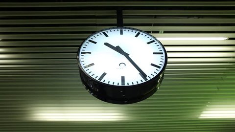 great modern round clock on a metal ceiling, black with white dial, black hands and time markings in the form of lines, ten at twenty-five minutes, 10:25 hours at the Railway Station