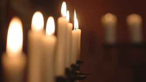 burning candles, one candle goes out and creates curls of thick smoke, the other candles burn evenly, on a dark background, high smooth candles have reduced the colors, transfer focus