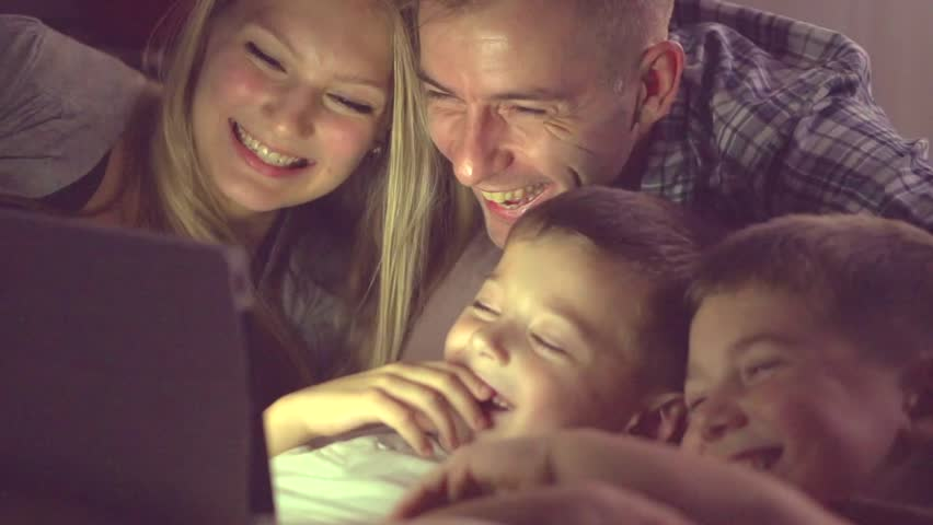 Happy family- Father, mother and Two kids lying down on the sofa and using tablet pc at night. Family watching movie on tablet computer in a dark room. HD 1080p, slow motion 240 fps, high speed camera | Shutterstock HD Video #14842066