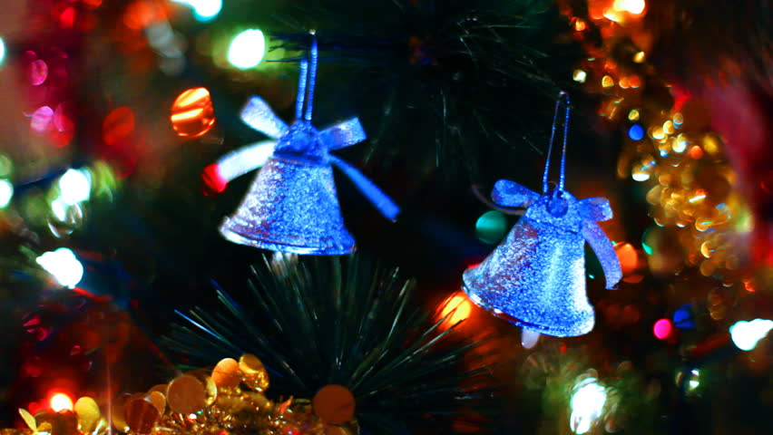 two blue toy bells hang on Christmas tree among of blinking colored garlands, close-up #1484446