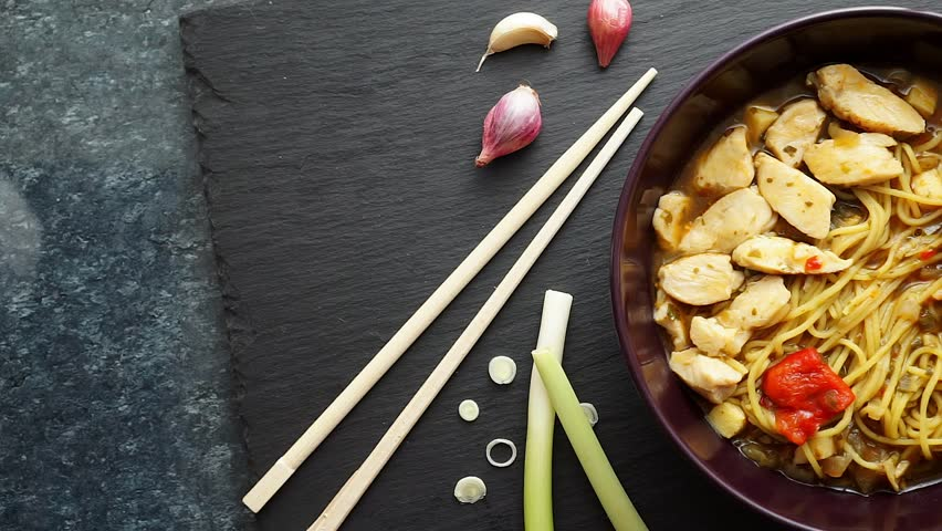 Panning video of a bowl with Ramen noodle soup with chicken, eggs, garlic and spring onion, on a dark slate background, with chopsticks