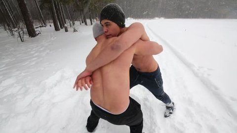 Two bare-chested guys wrestle standing at outdoor sportsground in winter forest.