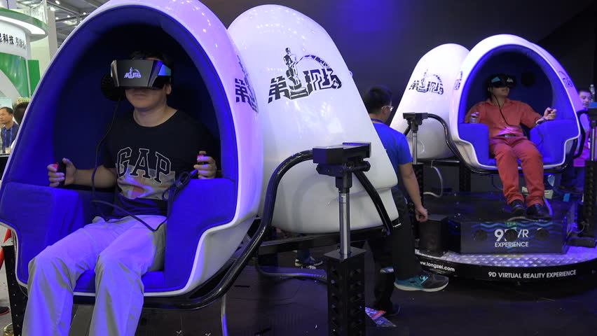 SHENZHEN, CHINA - 20 NOVEMBER 2015: People sit in moving egg shaped chairs, while wearing virtual reality glasses, at a trade show in Shenzhen, China