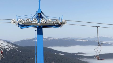 The blue bar of chair lift station on ski resort working and spinning isolate. Winter season in real time.