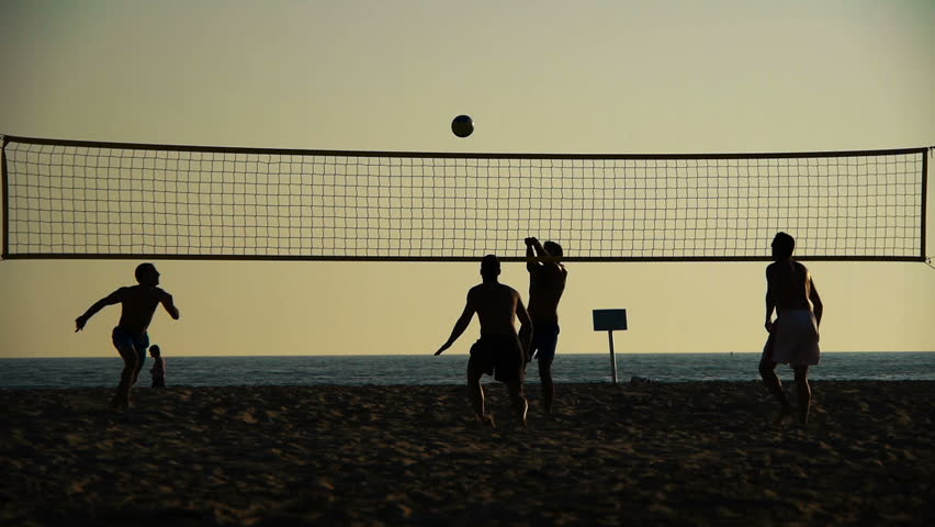 silhouette of volleyball players on the beach at sunset