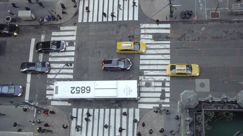overhead downward view of intersection in Midtown Manhattan with cars, taxis, bus and people from above in 4K NYC