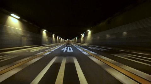 Driver POV entry to the Tokyo Bay Underpath on the Bayshore Freeway. Yellow and white lane stripes and random illumination through the tunnel.