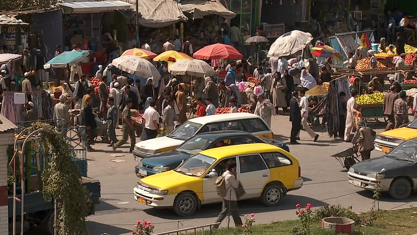 Taxis and vehicle traffic near a busy fruit market in Kabul, Afghanistan.