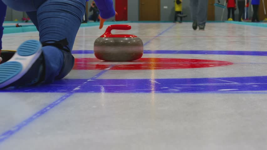 Curling player delivering a stone on a curling rink, sliding over the ice