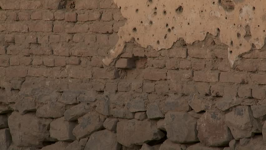 Tilt-up of bullet holes in a wall in Kabul, Afghanistan.