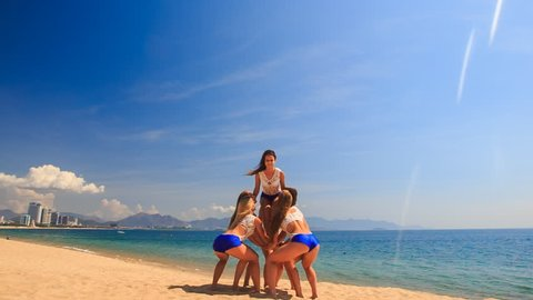 squad of cute cheerleaders in white blue uniform performs Back Tuck Basket Toss on beach against azure sea and sky