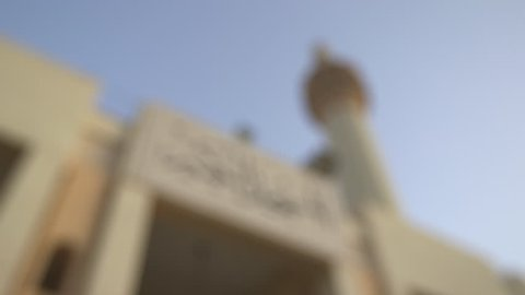 Kuwait Grand Mosque. Worm's eye view rack focus on the Andalusian style minaret and the entrance sign of the Grand Mosque in Arabic calligraphy.