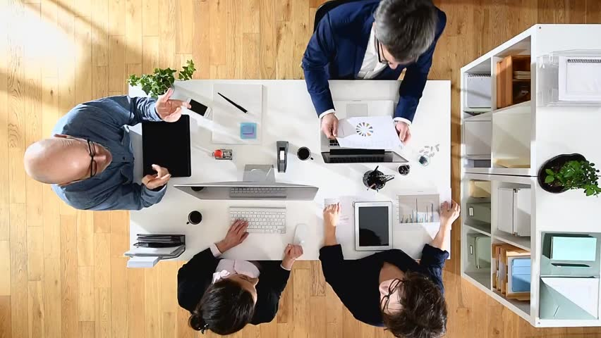 Top view. Meeting of business people, they are sitting around a table with their computers | Shutterstock HD Video #15049360
