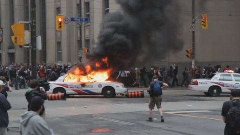 TORONTO, ONTARIO – JUNE 26th: Burning police car at the corner of Bay and King St on June 26th, 2010, Toronto, Ontario, Canada. Police and protesters clash at the G20 summit being held in Toronto.
