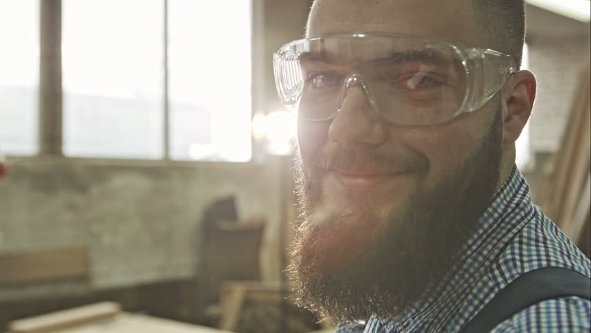 Closeup view of one handsome young adult man worker with a beard and goggles. RAW video record. | Shutterstock HD Video #15050116