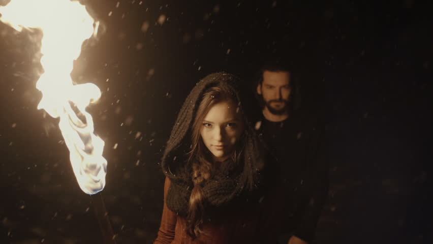 Portrait of a young mystic couple holding a torch in the dark forest. Mystery couple in the woods. Snowing. Slow motion.