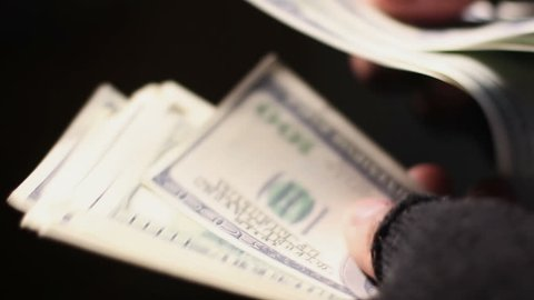 Closeup shot of male hands in shabby fingerless gloves counting cash in dollars