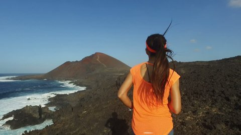 Trail running young woman runner exercising on rocky mountain path by sea. Fit female athlete working out in sportswear. ACTION CAMERA tracking shot. Lanzarote, Canary Islands, Spain