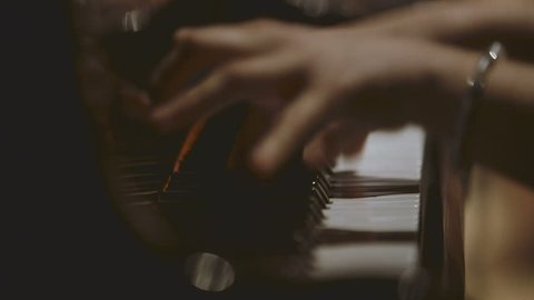 Close-up shot of woman's hands playing piano. Female pianist performing in concert. Focus is on her hands and piano keys. Female pianist performing in concert