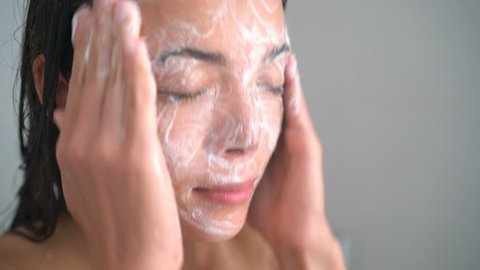 Skincare woman washing scrubbing face with facewash soap scrub in hot water shower. Closeup of Asian female young adult face cleaning skin.