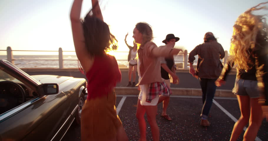 Group of multi-ethnic boho style friends partying and dancing at sunset on promenade with seaside behind them