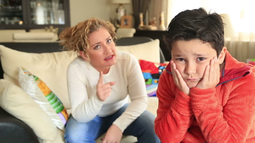 Mid adult mother scolding teenager son in living room at home