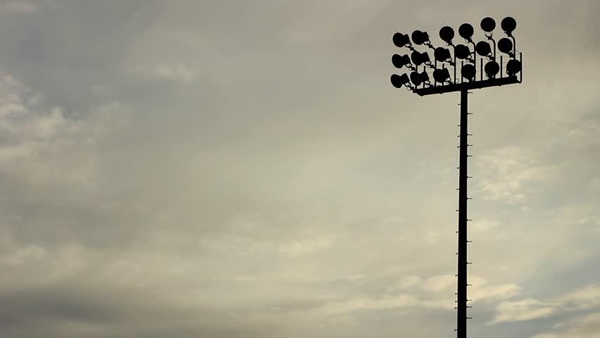 Pan of silhouetted stadium lights at sundown