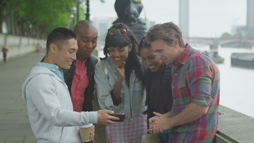 4K Happy mixed ethnicity group of friends looking at smartphone outdoors | Shutterstock HD Video #15183637