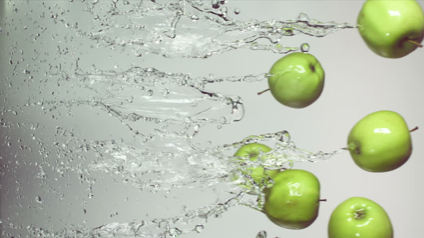Green apple with splashes of water on a white background, slow motion