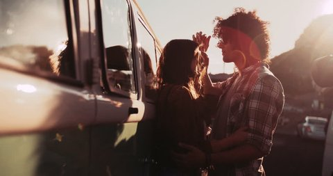 View through window of a Mixed Race Hipster Man and Hipster woman hugging in front of a retro van parked at s harbour