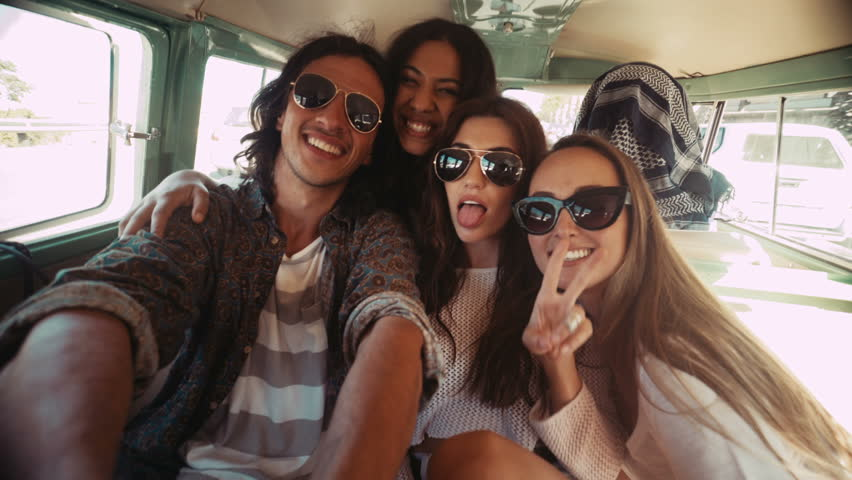 Three happy hipster young women taking selfie sitting in a vintage van during a summer road trip | Shutterstock HD Video #15255796