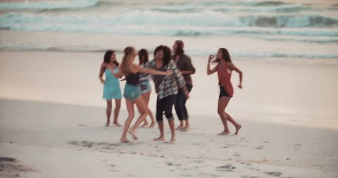 Hipster Multi-Ethic group of friends dancing together and moving in front of the sea on a sandy beach coastline